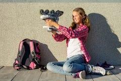 Dziewczyna nastoletnia siedzi na ściennym tle, obok jej plecaka Obraz Stock