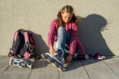 Dziewczyna nastoletnia usuwa sneakers i ubrania rolkowe łyżwy plenerowe Si Zdjęcie Royalty Free