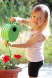 Dziewczyna nawadnia kwiaty Obraz Stock