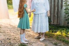 Dziewczyna obok starszej kobiety wnuczka pomaga jej babci dziewczyna w zielonej sukni trzyma clothespins dla mokrego odziewa zdjęcia royalty free