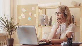 Dziewczyna od poparcia centrum opowiada na słuchawki i pisać na maszynie na laptop klawiaturze, zdjęcie wideo