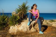 Dziewczyna odpoczywa po jogging na skale przy morzem Zdjęcie Royalty Free