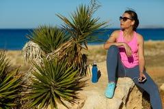 Dziewczyna odpoczywa po jogging na skale przy morzem Obraz Royalty Free