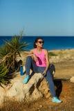 Dziewczyna odpoczywa po jogging na skale przy morzem Zdjęcia Stock