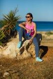 Dziewczyna odpoczywa po jogging na skale przy morzem Obrazy Stock