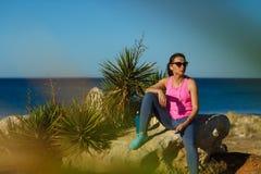 Dziewczyna odpoczywa po jogging na skale przy morzem Fotografia Royalty Free