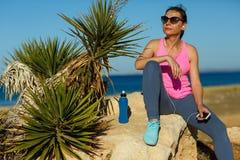 Dziewczyna odpoczywa po jogging na skale przy morzem Zdjęcia Royalty Free