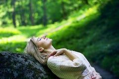 Dziewczyna odpoczywa w lesie na skale Fotografia Royalty Free
