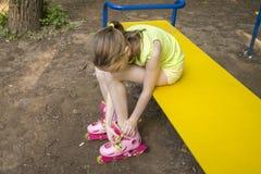 Dziewczyna odzieżowi rolowniki siedzi na parkowej ławce zdjęcie royalty free