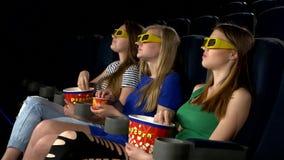Dziewczyna ogląda film przy kinem i je, 3d zdjęcie wideo