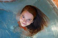 Dziewczyna ono uśmiecha się up przy kamerą podczas gdy siedzący w basenie obrazy royalty free