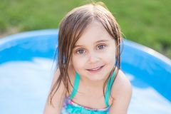 Dziewczyna ono uśmiecha się w kiddie basenie zdjęcie royalty free