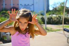 Dziewczyna ono uśmiecha się w różowym stroju robić plauful gestowi Obraz Stock
