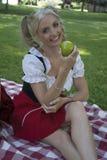 Dziewczyna ono uśmiecha się z jabłkiem zdjęcia royalty free
