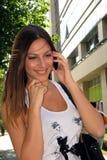 Dziewczyna ono uśmiecha się z mobilny opowiadać Fotografia Royalty Free