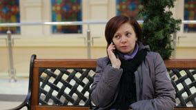 Dziewczyna opowiada mądrze telefonu miejsca siedzące przy ławką zbiory