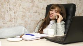 Dziewczyna opowiada na smartphone z fili?anka kawy w r?ce przy prac? w biurze robota komputera pi?kna kobieta jednostek gospodarc zbiory