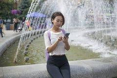 Dziewczyna opowiada na telefonie pisze wiadomości na internecie obraz stock