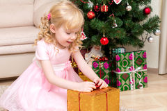 Dziewczyna otwiera prezent w złocistym opakowaniu Zdjęcia Royalty Free