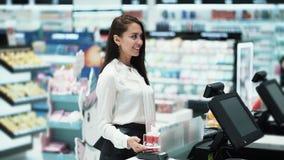 Dziewczyna płaci dla zakupów używać telefon, contactless płatnicza technologia, zwolnione tempo zdjęcie wideo