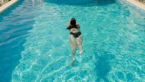 Dziewczyna pływa w plenerowym basenie przy hotelem w czarnym swimsuit zdjęcie wideo