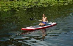 Dziewczyna paddling na kanale w mieście w czółnie obraz stock