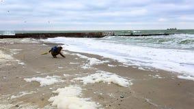 Dziewczyna patrzeje burzową denną pozycję na piaskowatej plaży zdjęcie wideo