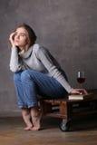 Dziewczyna patrzeje daleko od z książką i winem Szary tło Obrazy Stock