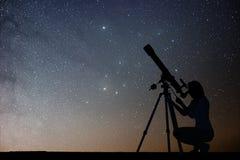Dziewczyna patrzeje gwiazdy z teleskopem Milky sposobu galaxy Obrazy Stock