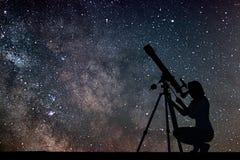 Dziewczyna patrzeje gwiazdy z teleskopem Milky sposobu galaxy Fotografia Stock