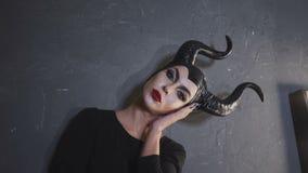 Dziewczyna patrzeje kamerę bezpośrednio w wizerunku Maleficent z wielkimi czarnymi poroże i czerwoną pomadką zbiory wideo