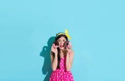 Dziewczyna patrzeje kamerę i pokazuje słodkich pączki Zdjęcie Stock