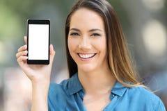 Dziewczyna patrzeje kamerę pokazuje mądrze telefonu ekran zdjęcie royalty free