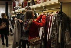 Dziewczyna patrzeje kurtki w sklepie odzieżowym Zdjęcia Stock