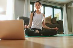 Dziewczyna patrzeje laptop i robi joga w domu zdjęcia stock