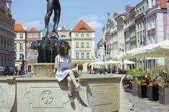 Dziewczyna patrzeje mapy obsiadanie fontanną Zdjęcia Stock