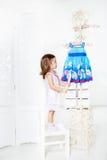 Dziewczyna patrzeje na żakieta stojaku Zdjęcia Royalty Free