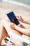 Dziewczyna patrzeje pastylka komputer osobistego na plaży Fotografia Royalty Free