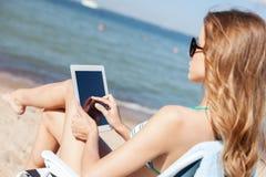Dziewczyna patrzeje pastylka komputer osobistego na plaży Obrazy Royalty Free