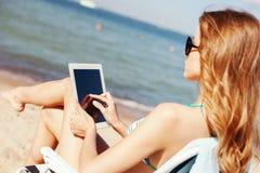 Dziewczyna patrzeje pastylka komputer osobistego na plaży Zdjęcie Stock