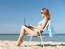 Dziewczyna patrzeje pastylka komputer osobistego na plaży Zdjęcia Stock