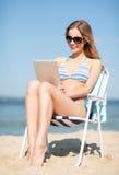 Dziewczyna patrzeje pastylka komputer osobistego na plaży Obrazy Stock