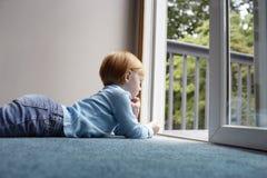 Dziewczyna Patrzeje Przez balkonu Podczas gdy Kłamający Na dywanie Zdjęcie Stock