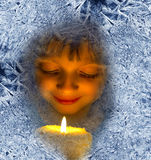 Dziewczyna patrzeje przez frosted okno z świeczkami Zdjęcie Royalty Free