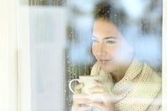 Dziewczyna patrzeje przez nadokiennej mienie kawy w zimie obraz royalty free