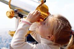 Dziewczyna patrzeje przez teleskopu Zdjęcia Stock