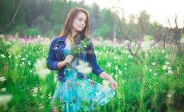 Dziewczyna patrzeje puszek na tle kwiat łąki z uśmiechem obraz stock