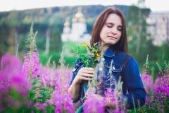 Dziewczyna patrzeje puszek na tle kwiat łąki z uśmiechem zdjęcia stock