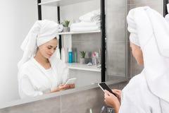 Dziewczyna patrzeje smartphone w łazience zdjęcia royalty free