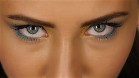 Dziewczyna patrzeje uważnie up z piękny jaskrawym i ostrzy oczami uzupełniał z bliska zdjęcie wideo
